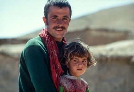 Kudish man and small girl on donkey.